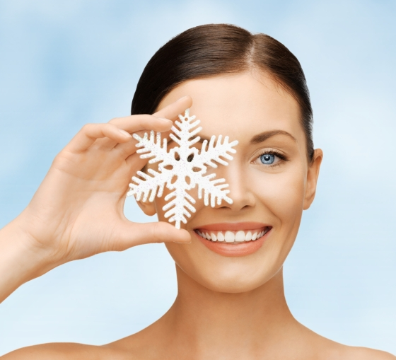 Woman holding up a snowflake in front of well cared for skin