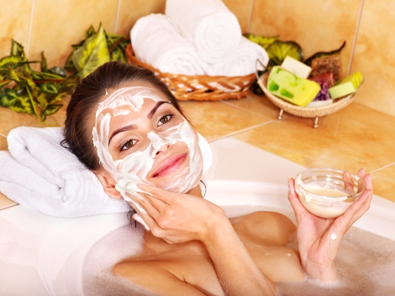 Woman taking a bath and applying a homemade face mask