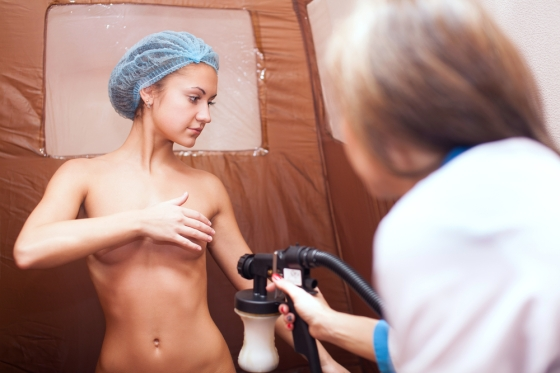 Young woman getting spray tanned by a technician