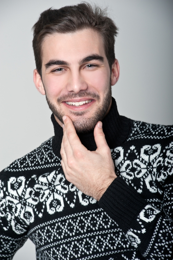 Man in sweater stroking his beard