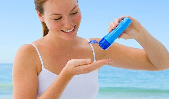 Woman Putting Sunscreen in her Hand Before Applying to Body