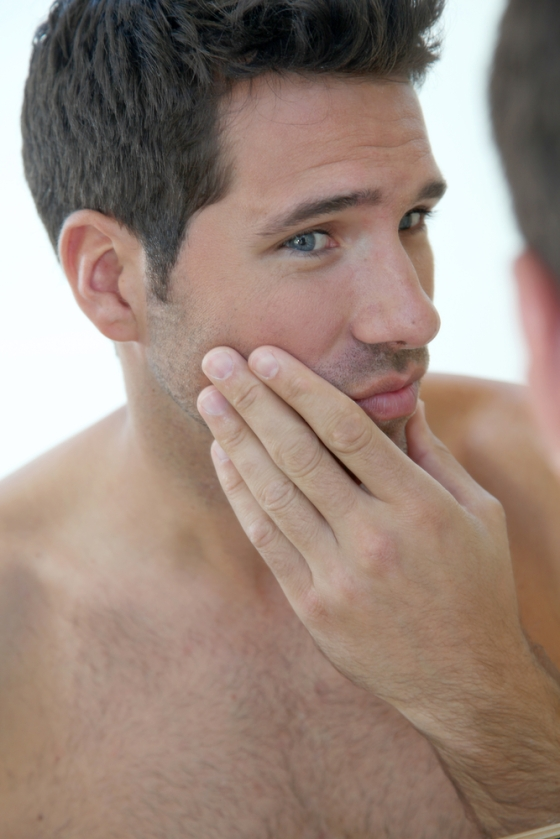 Young man looking at beard in mirror