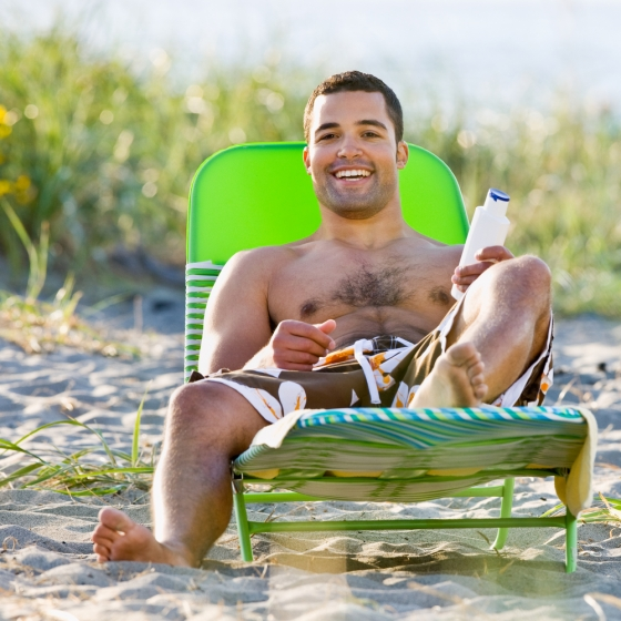 Young man on the beach with sunscreen