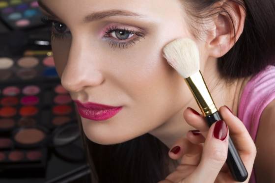 Young lady applying shimmer makeup