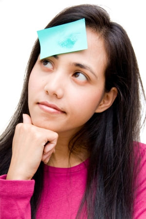 Young lady with blotting paper stuck to her forehead