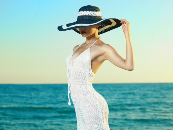 Beautiful young lady in white dress and sun hat