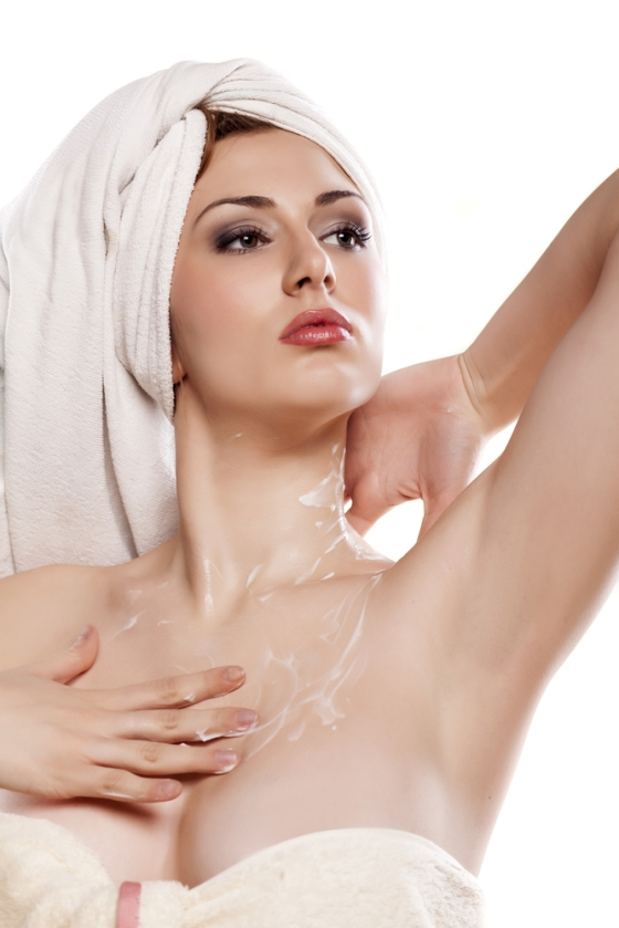 Woman applying cream to neck and chest after bathing