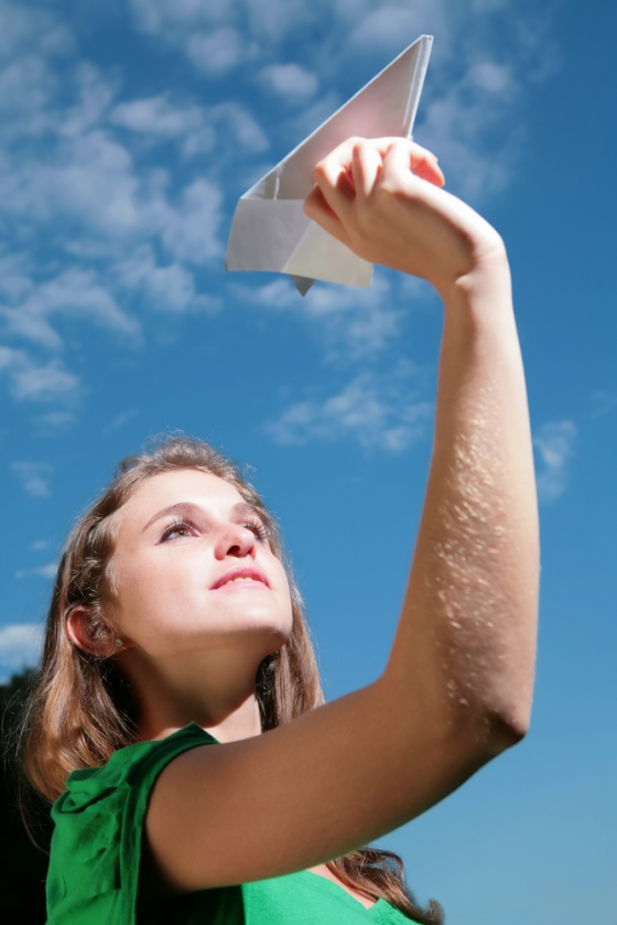 Girl throwing paper airplane in the sky