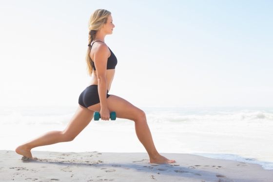 Woman doing lunges on the beach with weights