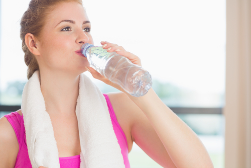 Fitness girl drinking from bottle of water