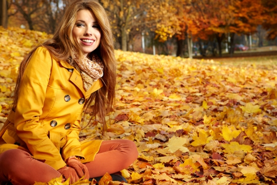 Young woman sitting in a pile of leaves wearing fall fashions