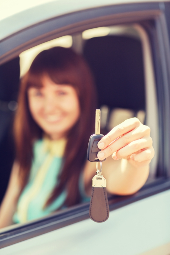 Young woman showing off the keys to her new car