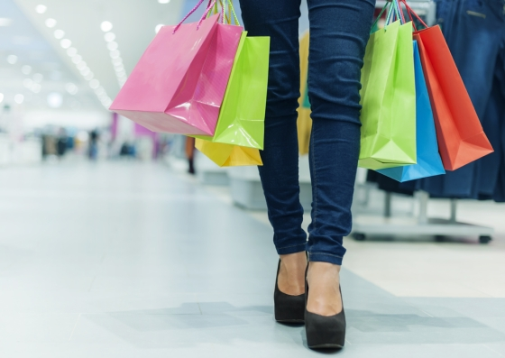Womans legs and feet show shopping in a store with shopping bags