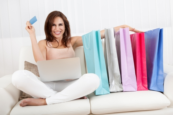 Woman shopping on her laptop with her shopping bags near her