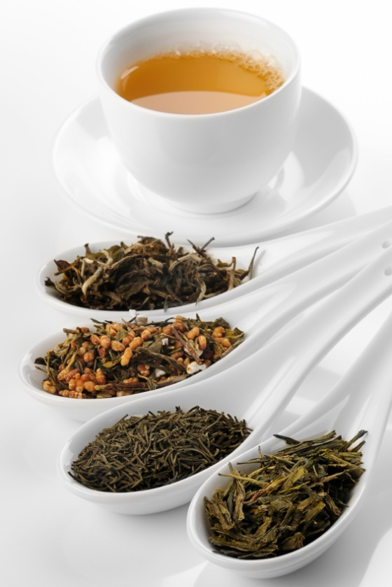 Cup of green tea with spoons full of various types of green tea