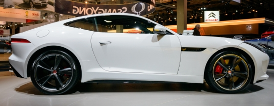 White Jaguar F-type coupe sports car and classic yellow Jaguar E-type on display at the 2014 Brussels motor show. People in the background are looking at the cars.