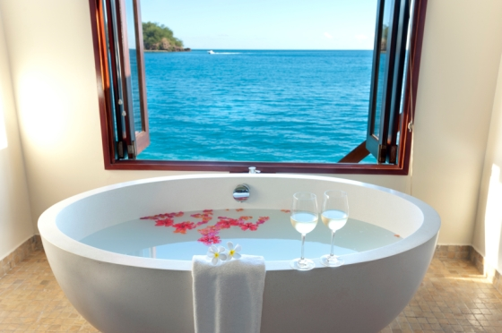 Luxury bathroom at over water resort with view of the ocean with wine