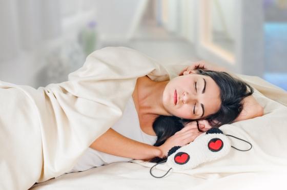 Beautiful brunette sleeping in a beige bed.