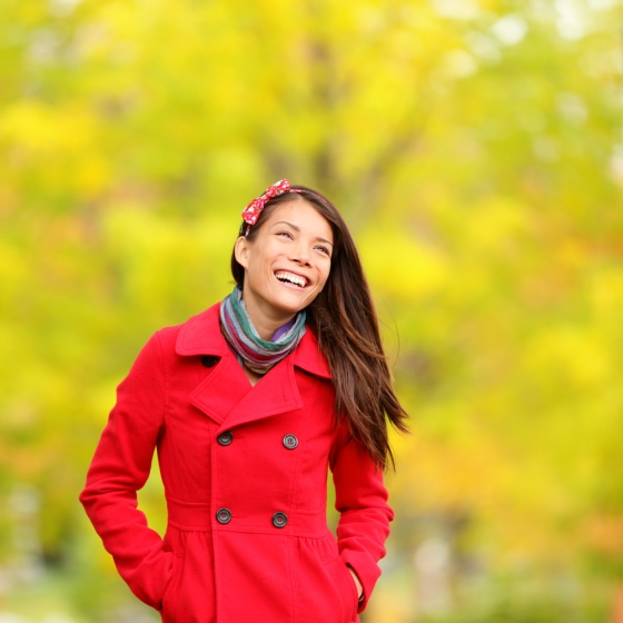 Woman wearing a red colored trench coat in a spring background.