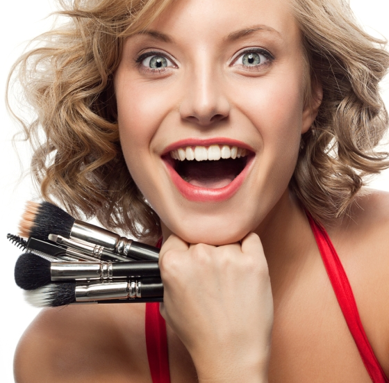 Beautiful woman excited with her makeup brushes