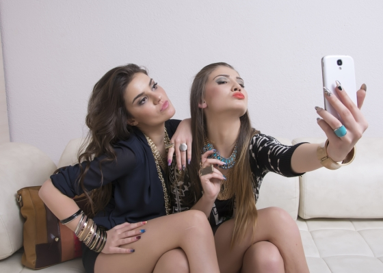 Woman showing off her pout clicks a selfie with her friend.