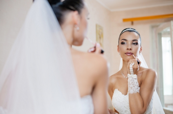 Bride looks at herself in the mirror and applies lipstick.