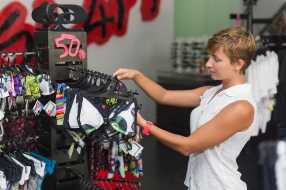 Woman selecting a swimsuit while shopping.