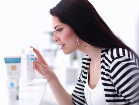 Woman choosing skin care products at a beauty store.