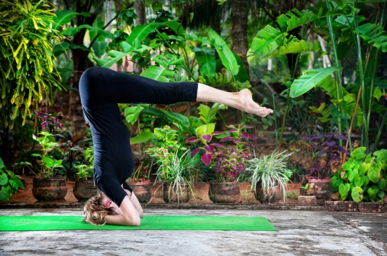 Woman performing the Shirshasana in her backyard.