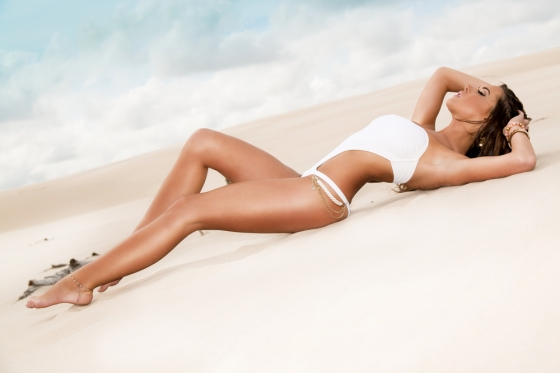 Woman with a beautiful tan lying on a beach.