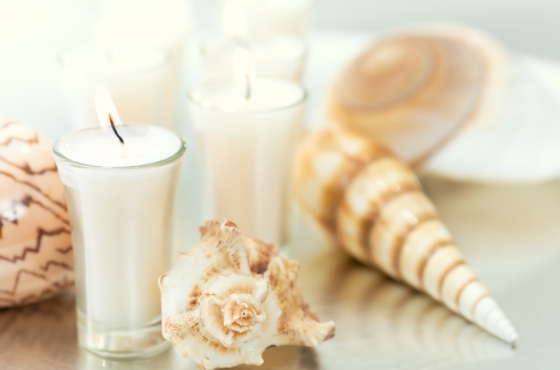 Picture of lit candles and seashells.