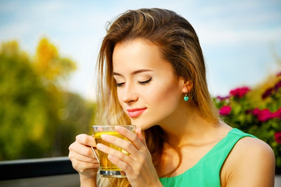 Woman having green tea in a natural background.