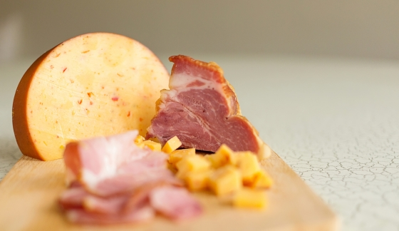 Cheese and ham on a chopping board.
