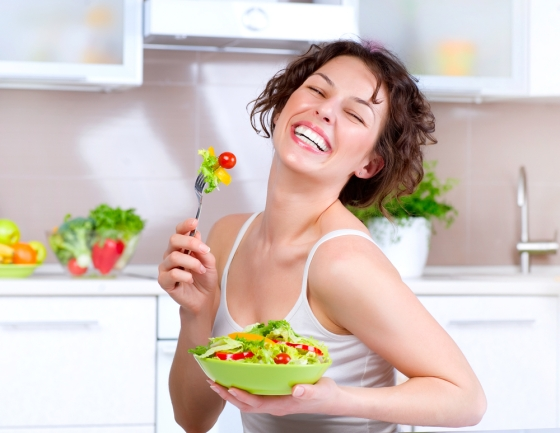 Woman eating a fresh vegetable salad with a fork.