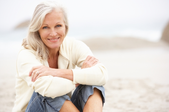 Woman in her fifties sitting in a beach.