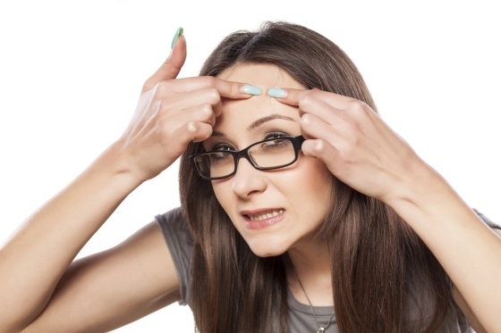 Woman wearing spectacles sqeezing her pimple.
