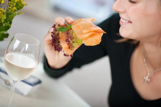Woman enjoying wine and salmon on bread.