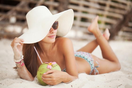 Woman sipping on coconut water in a beach.