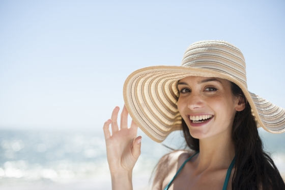 Woman wearing a broad rimmed hat in a beach