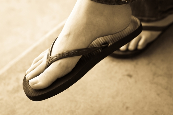 Closeup of woman with beautiful legs wearing slippers.