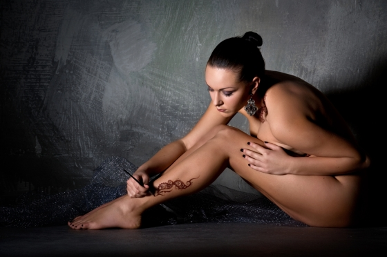 Woman applying a tattoo on her legs