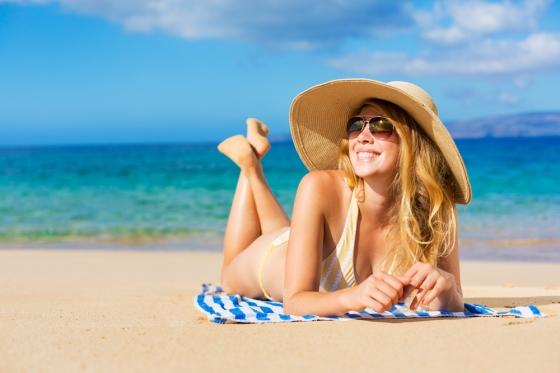 Woman sunbathing in a beach.