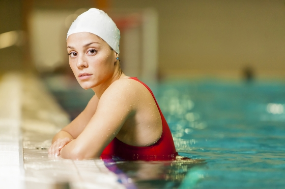 Woman wearing a swimming cap in a pool.