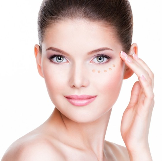 Woman applying eye gel on her under-eye area.