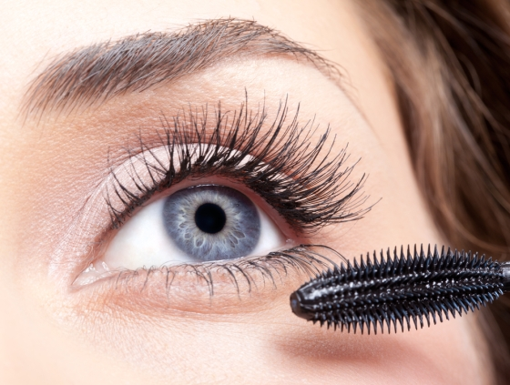 Closeup of a woman applying mascara.