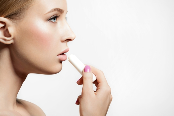 Woman applying lip balm.