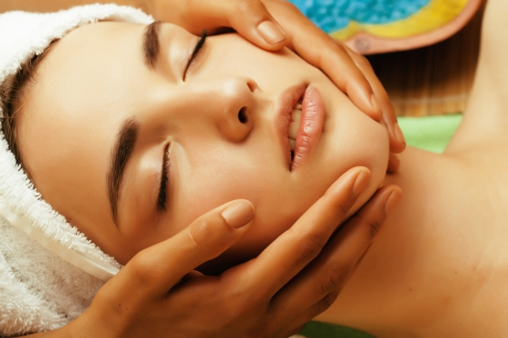 Woman enjoying a facial massage in a spa.