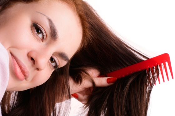 Woman using a wide toothed comb to comb her hair.