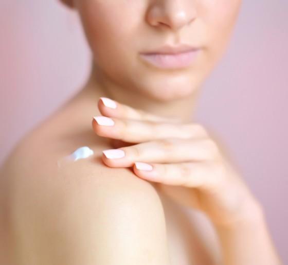 Woman applying moisturizer on her body