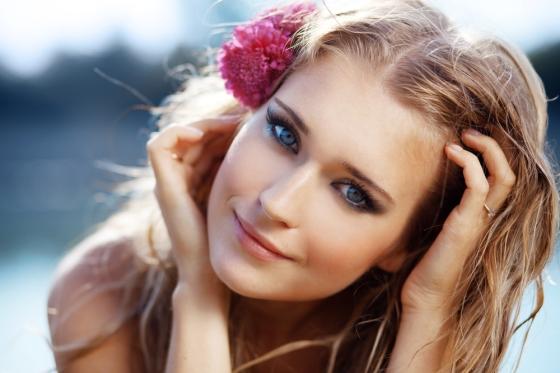Woman using a tropical flower as a hair accessory
